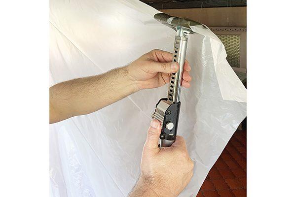 Nun betätigen Sie die Lösetaste und ziehen die Teleskopstange soweit heraus bis sich Abstützfläche und Decke berühren. Danach ziehen Sie den unteren Teil der Folie unter die Abstützfläche der Deckenstütze am Boden.