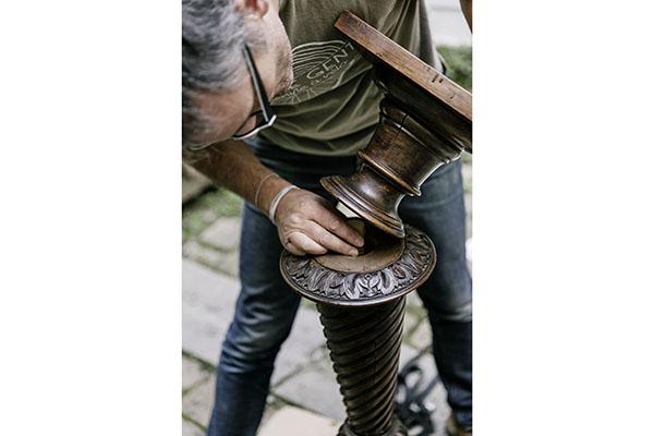 Philippe Genty restauriert den antiken Holzsockel und verzapft ihn fachmännisch direkt vor Ort beim Kunden.
